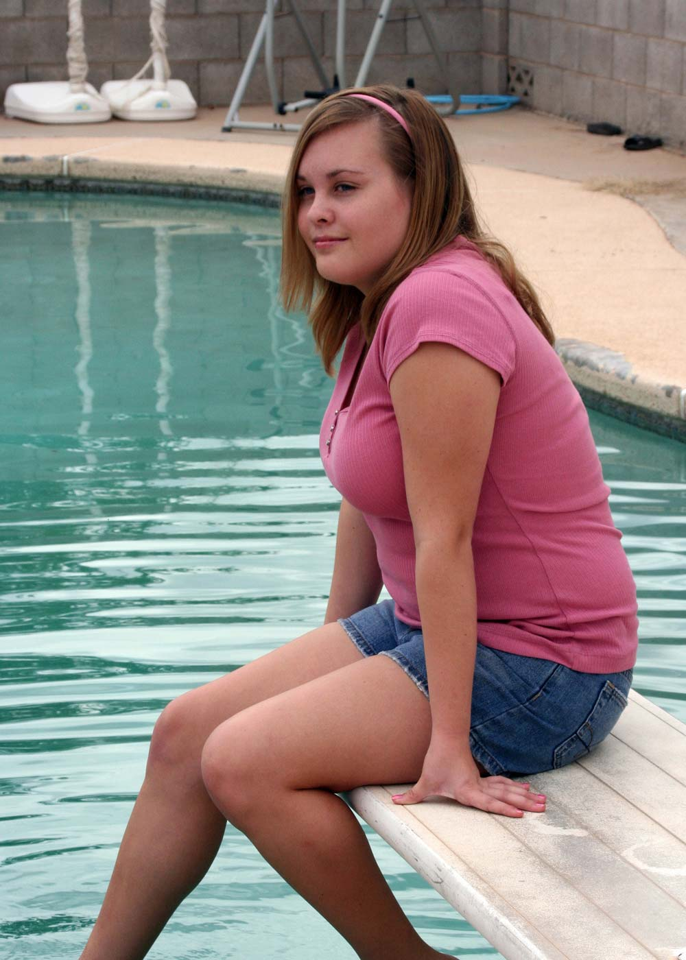 Fat girl sitting down on a pool image editing